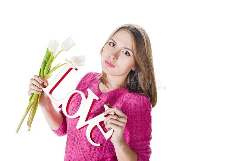 Blond flicka med dekorativa ordförälskelse- och vittulpan royaltyfri fotografi
