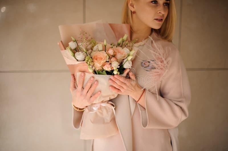 Blond flicka med en bukett av rosor arkivbild