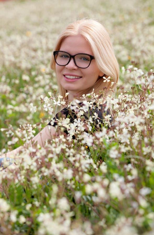 Blond flicka med exponeringsglas som omges av blommor arkivfoton