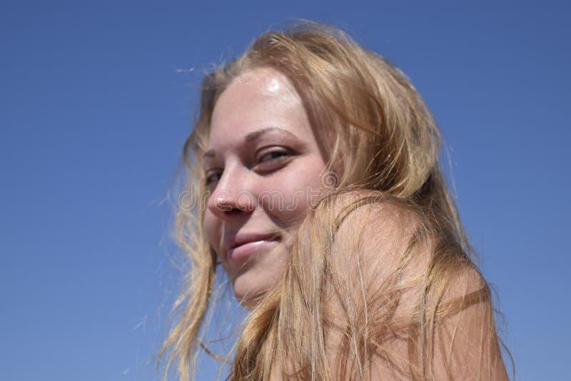Blond flicka med hennes hår på bakgrund för blå himmel härligt kvinnabarn royaltyfri bild
