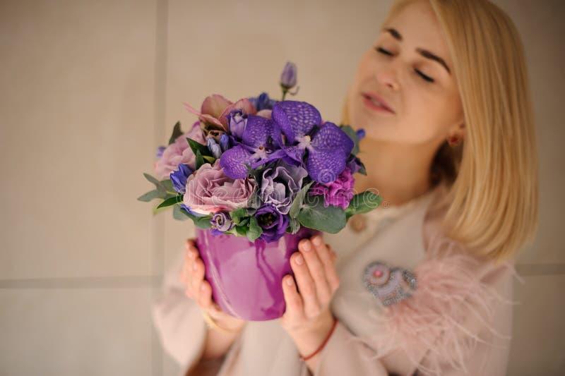Blond flicka med iriers i blomkruka royaltyfri fotografi