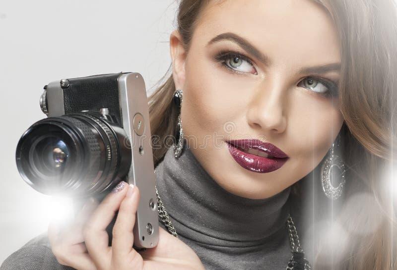 Blond flicka med kameran som framåtriktat ser Härlig blond flicka med den svarta retro kameran i studio mot den vita väggen Sinnl royaltyfria foton