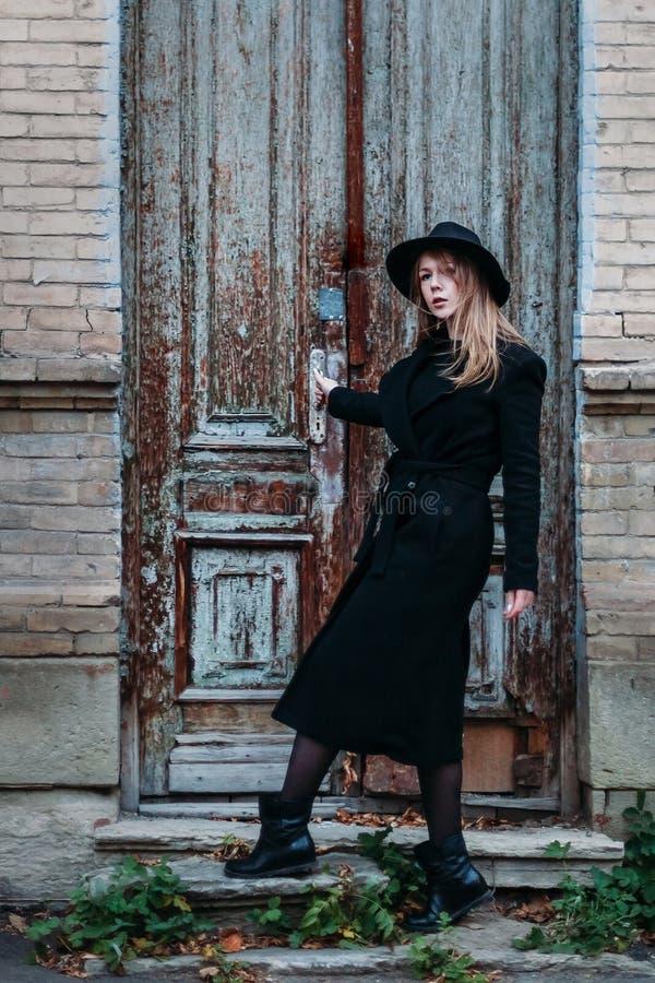 Blond flicka med långt hår, i svart lag i hatt, ställningar på bakgrunden av huset för tegelsten för antik gammal trädörr för tap royaltyfria bilder