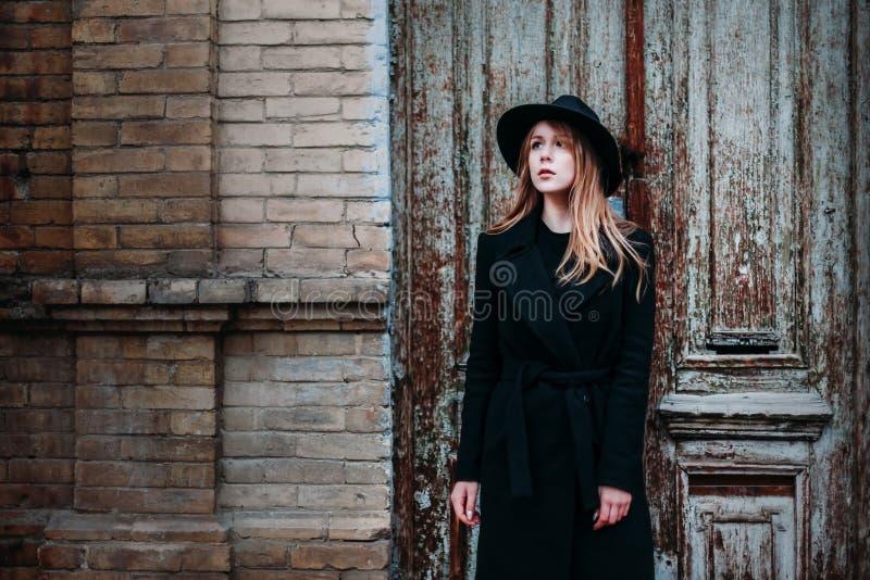 Blond flicka med långt hår, i svart lag i hatt, ställningar på bakgrunden av huset för tegelsten för antik gammal trädörr för tap royaltyfri foto