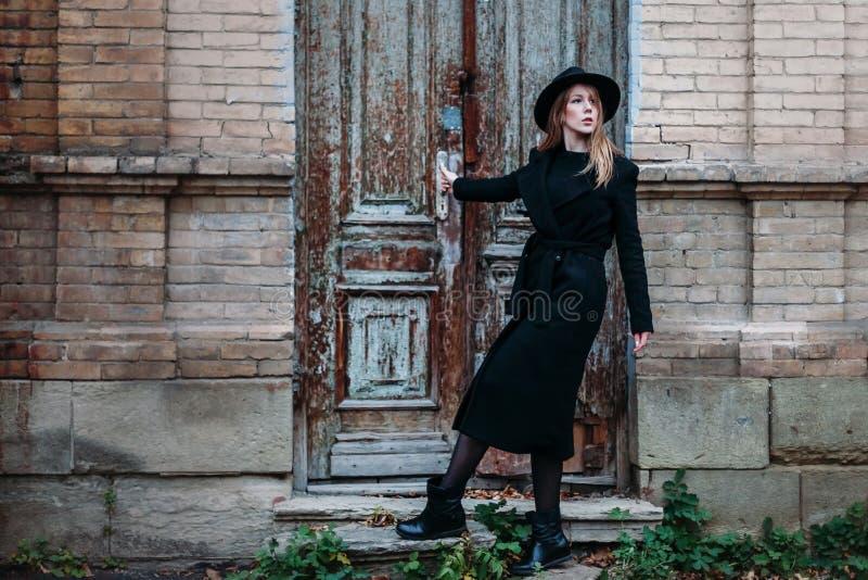 Blond flicka med långt hår, i svart lag i hatt, ställningar på bakgrunden av huset för tegelsten för antik gammal trädörr för tap arkivbild
