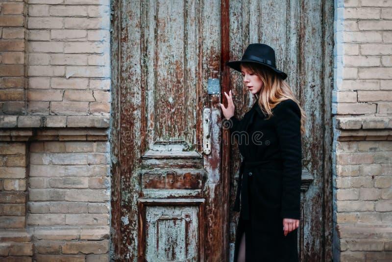 Blond flicka med långt hår, i svart lag i hatt, ställningar på bakgrunden av huset för tegelsten för antik gammal trädörr för tap fotografering för bildbyråer