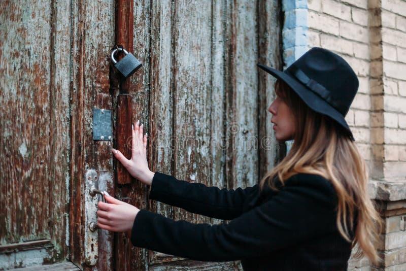 Blond flicka med långt hår, i svart lag i hatten som försöker att öppna en låst dörr av huset för tegelsten för antik gammal träd arkivfoto