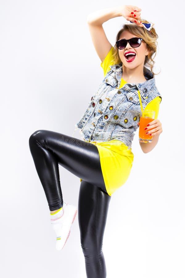 Blond flicka med orange fruktsaft och sugrör Bärande grov bomullstvillväst och solglasögon royaltyfri foto