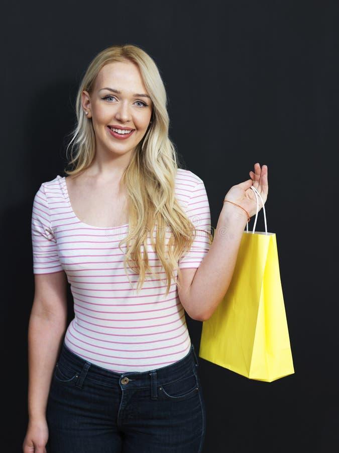 Blond flicka med shoppingpåsar på en svart tavlabakgrund arkivfoton