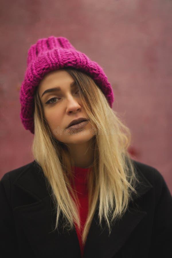 Blond flicka med stora ögon och fylliga kanter mot en rosa bakgrund arkivfoton