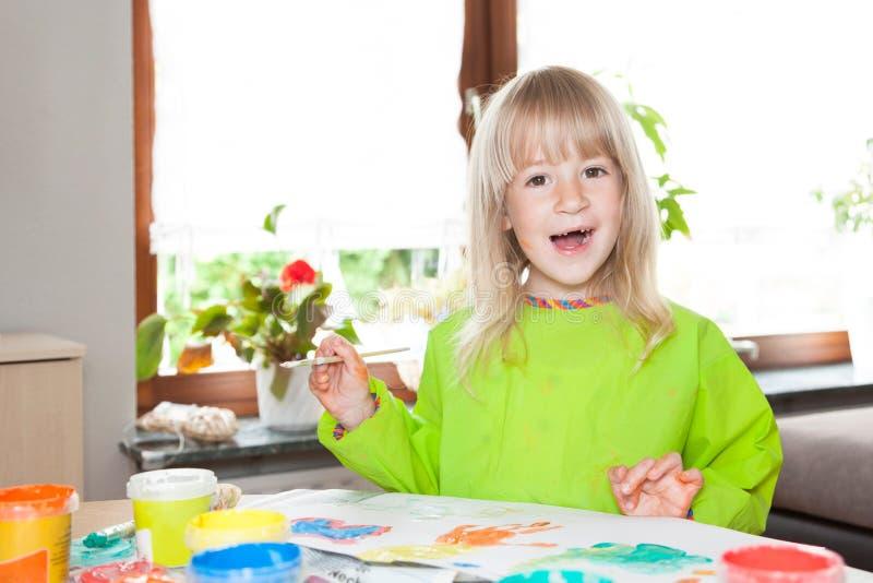 Blond flicka med vattenfärger royaltyfria bilder