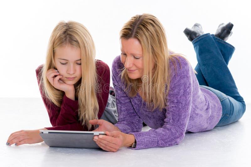 Blond flicka och hennes moder som använder minnestavlaPC arkivfoton