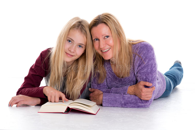 Blond flicka och hennes moder som använder minnestavlaPC royaltyfri fotografi