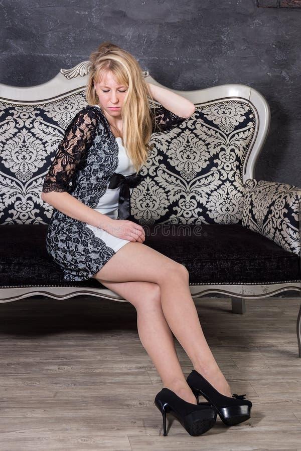 Blond flicka på soffan arkivfoto