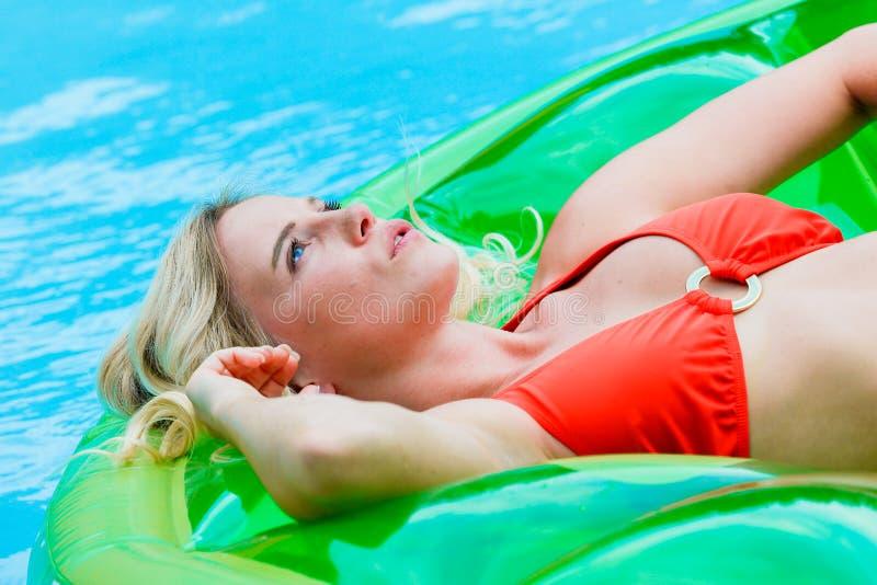 Blond flicka på uppblåsbar i pöl arkivfoton