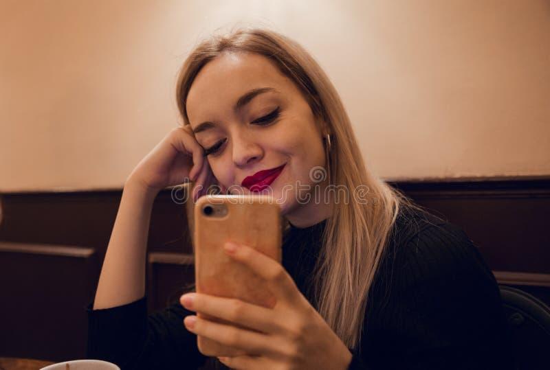 Blond flicka som använder mobiltelefonen royaltyfri fotografi