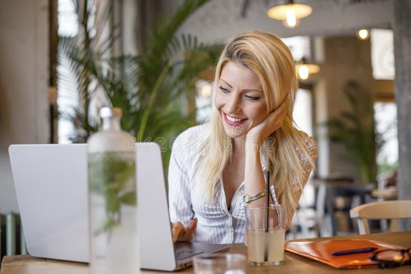 Blond flicka som framme sitter av datoren fotografering för bildbyråer