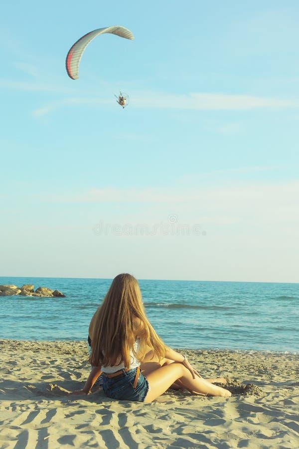 Blond flicka som framme sitter av havet som ser den lilla paraglidingmotorn royaltyfri bild