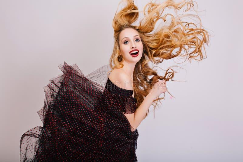 Blond flicka som har roligt härligt långt lockigt hår i luften, ung kvinna som poserar på studion Rolig blick med den öppnade mun royaltyfria bilder
