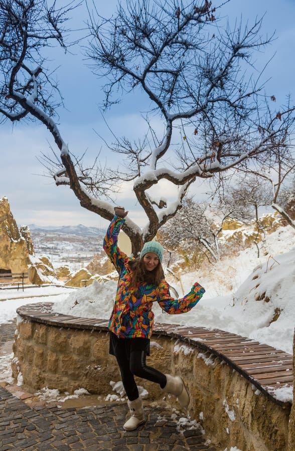 Blond flicka som ler med långt hår, den bärande pälshatten, pälsanoraken och läderhandskar, i vinterbergmiljö med arkivfoto