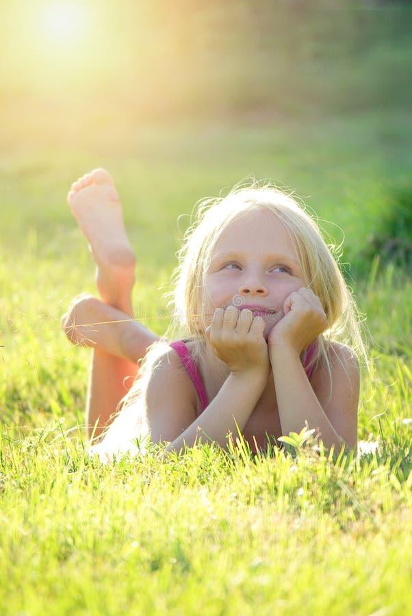 Blond flicka som ler och ligger på gräset på sommarsolnedgången som ser himlen Naturlig lycka, gyckel och harmoni arkivbild
