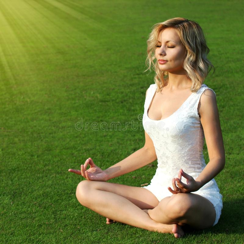 Blond flicka som mediterar på grönt gräs. Härlig placering för den unga kvinnan i yoga poserar av lotusblomma i parkera. royaltyfri fotografi