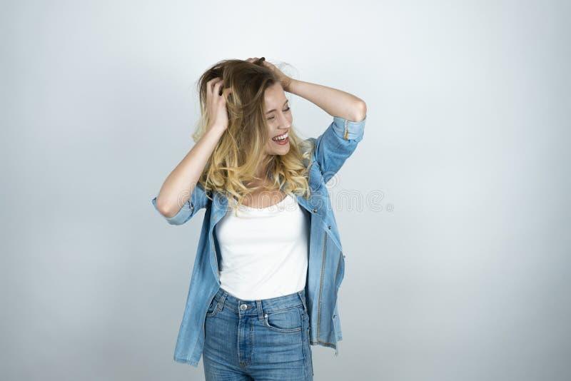 Blond flicka som rymmer händer nära förvånade huvudblickar le vit isolerad bakgrund arkivbild