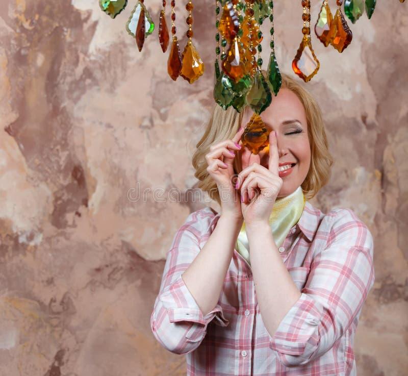Blond flicka som ser till och med den genomskinliga hängande stenen royaltyfri foto