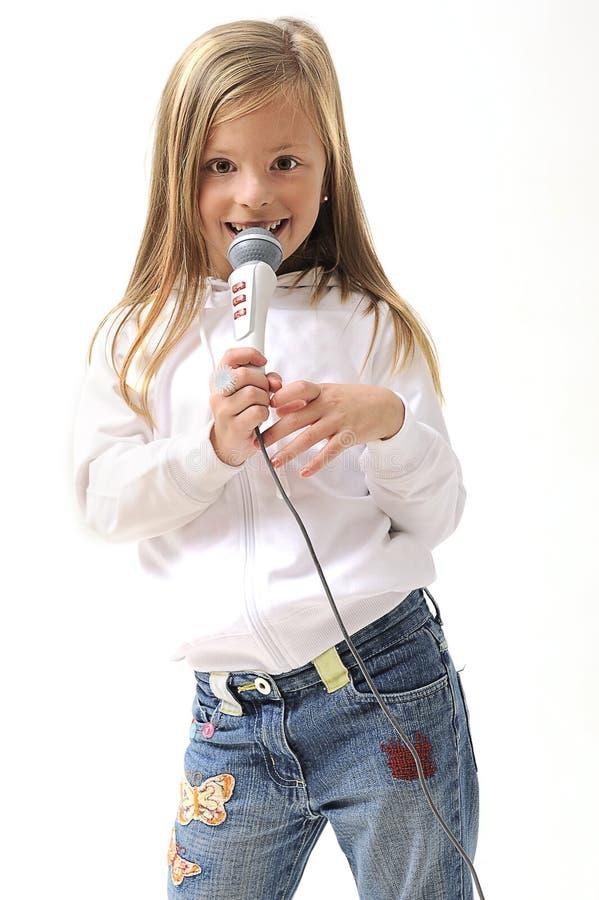 blond flickamikrofon som sjunger genom att använda arkivbild