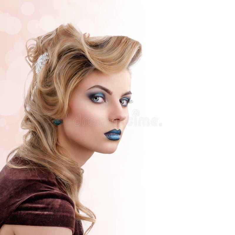 Blond flickastående för skönhet med färgrik makeup arkivfoto