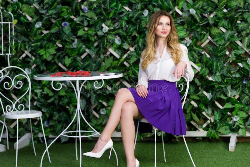Blond flickastående i utomhus- kafé royaltyfria bilder