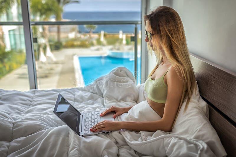 Blond frilans- kvinnablogger DET som skriver på bärbara datorn Flickan som skriver på bärbara datorn, gör hon läxa på netbook, fe royaltyfri bild