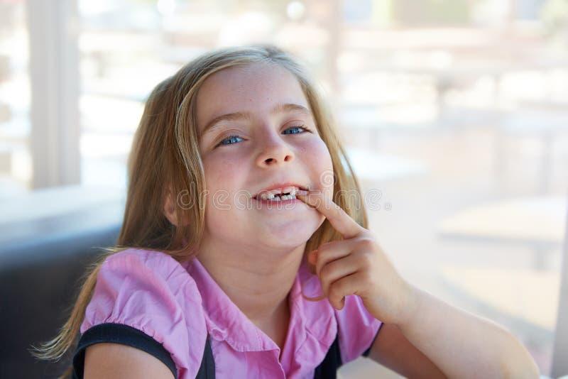 Blond gelukkig jong geitjemeisje die haar gekartelde tanden tonen royalty-vrije stock afbeelding