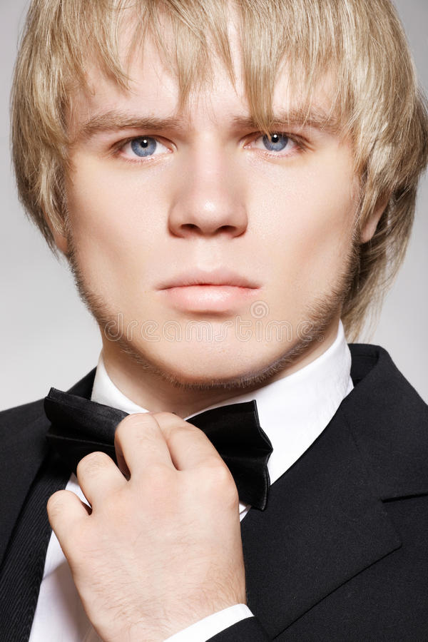 Blond gentleman in elegant black suit with bow-tie. Close-up portrait of blond man model in elegant black suit with bow-tie on gray background stock photo