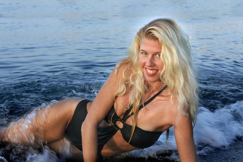 Blond girl in black bikini lying on the beach and the waves splash on it royalty free stock photos