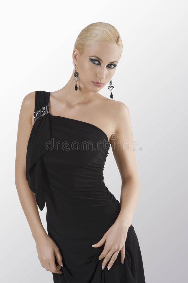 Blond girl in black dress posing and holding. Blond attractive young woaman in black dress and black earring looking in camera with strong and eyes posing stock image
