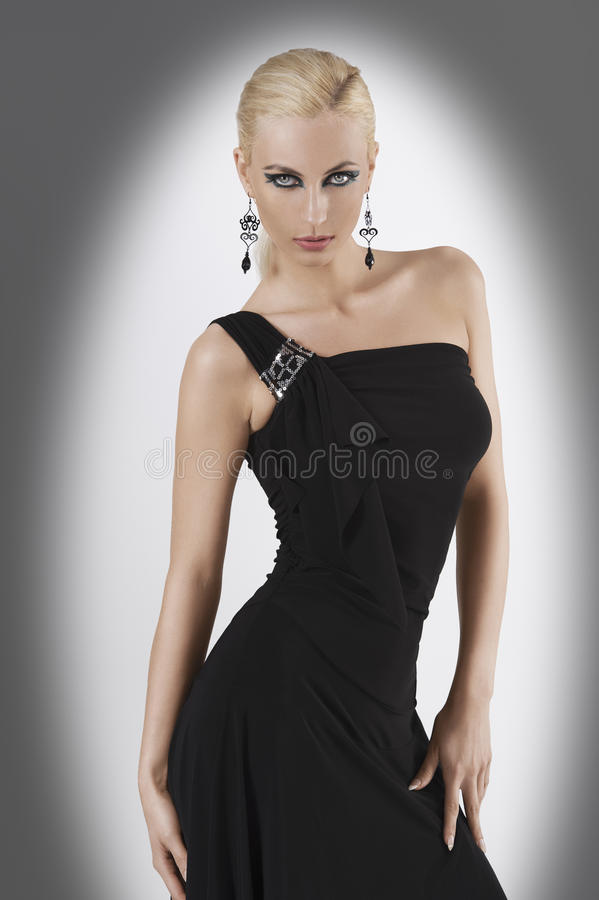 Blond girl in black dress with pose. Blond attractive young woaman in black dress and black earring looking in camera with strong and eyes and wit pose looking royalty free stock photos