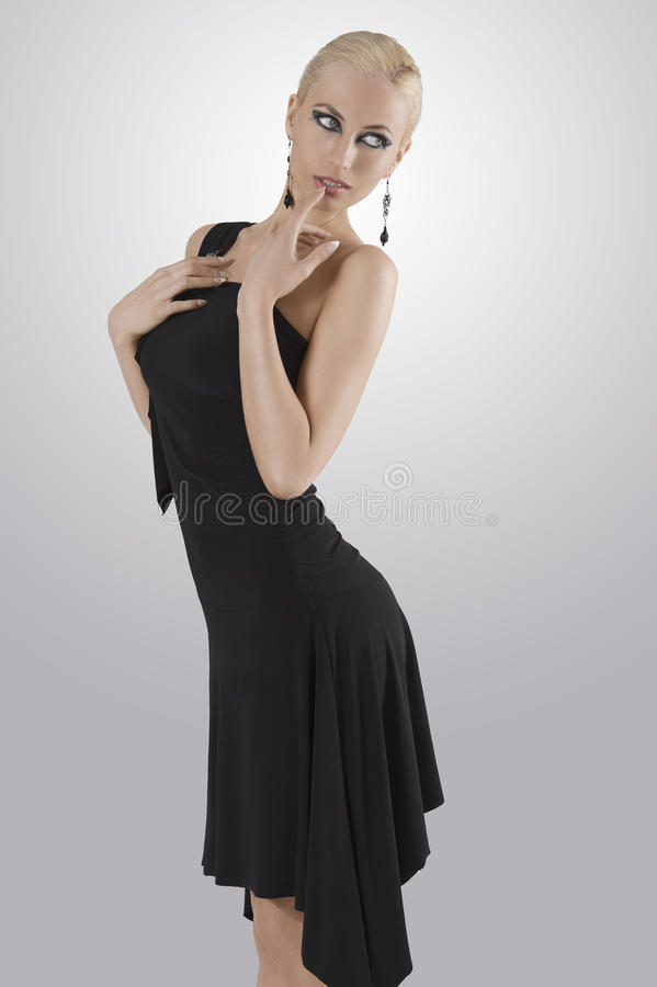Blond girl in black dress standing with pose. Blond attractive young woaman in black dress and black earring looking in camera with strong and eyes standing with royalty free stock photos