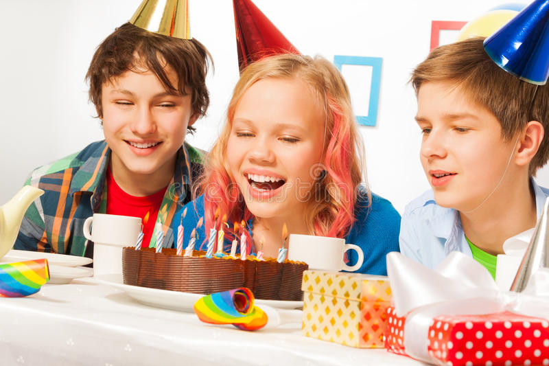 Blond girl blows candles on her birthday cake. Happy teen girl blow candles on birthday cake with smiling friends on a party table and presents and decorations stock images