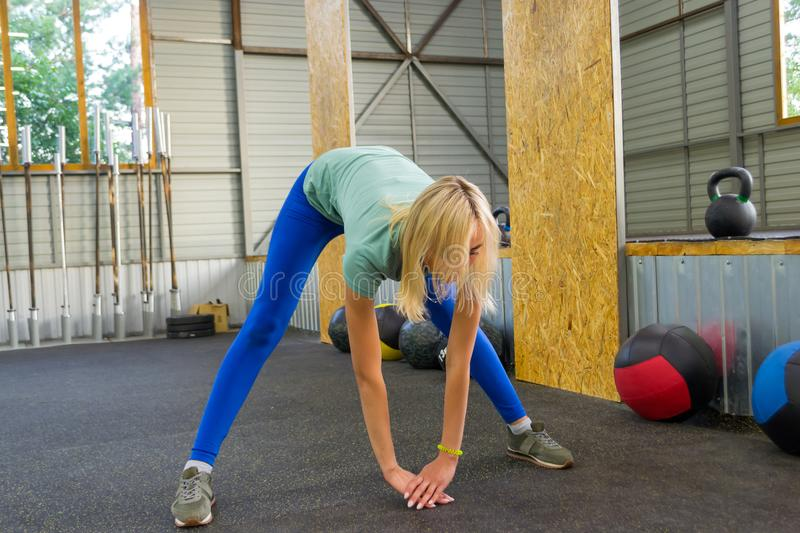The blond girl in blue leggings in the gym is training, leaning stock photos