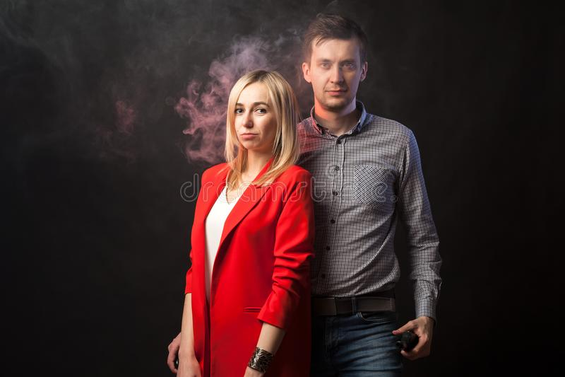 Blond girl in brightly red suit with jacket and white blouse and tall dark-haired guy royalty free stock images