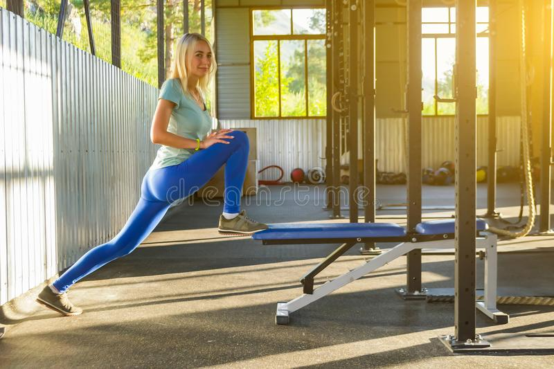 Blond girl is doing stretching by raising her leg and leaning ag stock photography