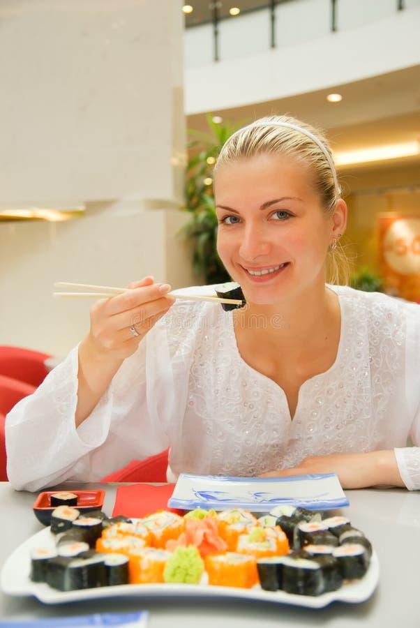 Blond girl eats sushi stock photos