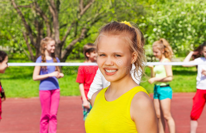 Blond girl and friends playing volleyball behind stock photography