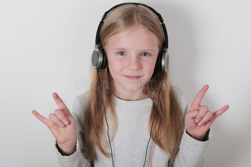 Blond girl with headphones listening music and singing. Cute little girl making a rock-n-roll sign. stock images