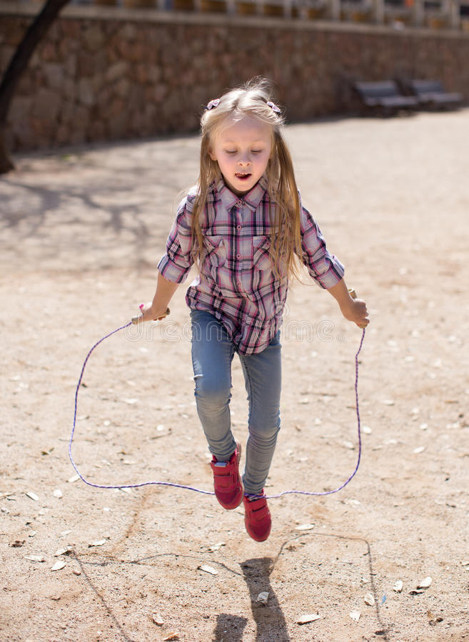 Blond girl jumping rope. Nice blond girl jumping rope royalty free stock photos