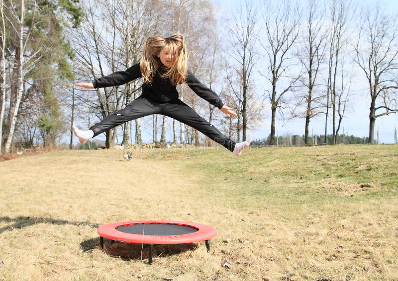 Blond girl jumping on trampoline. Blond girl - hairy kid in black clothes jumping on black and red kids´ small trampoline standing on grass of meadow stock photography