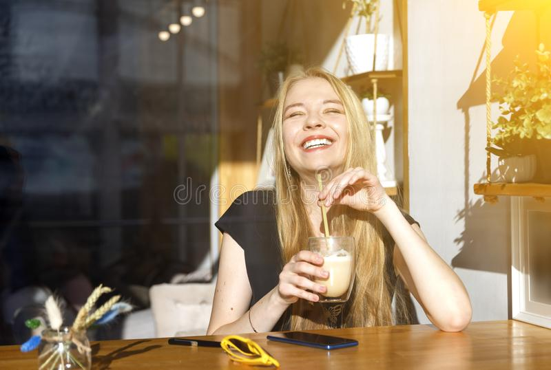 Laughing blond girl holding latte in glass with straw royalty free stock photo