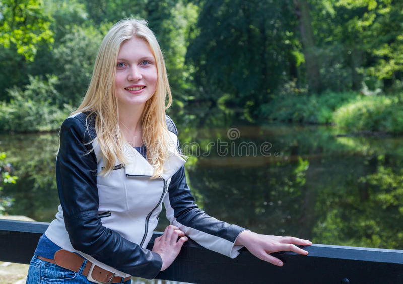 Blond girl leaning on fence near water in forest royalty free stock photos