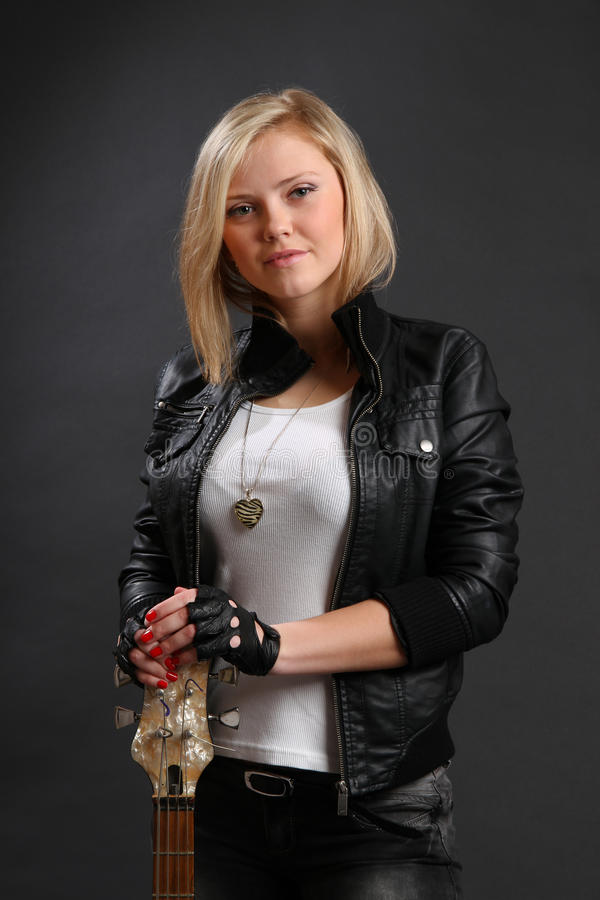Blond girl in leather jacket with guitar royalty free stock photography